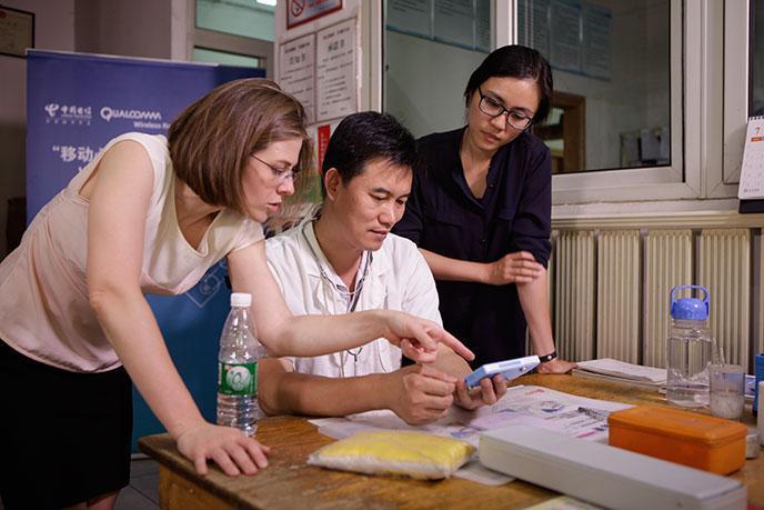 任医生向Lauren和Lynn 展示心电图传感智能手机的工作原理